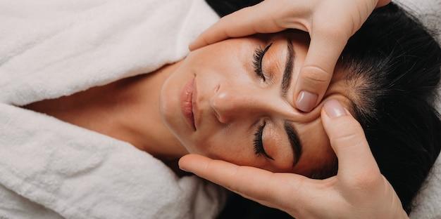 Bovenaanzicht portret van brunette dame liggend op de bank en met een gezichtsmassage in de salon