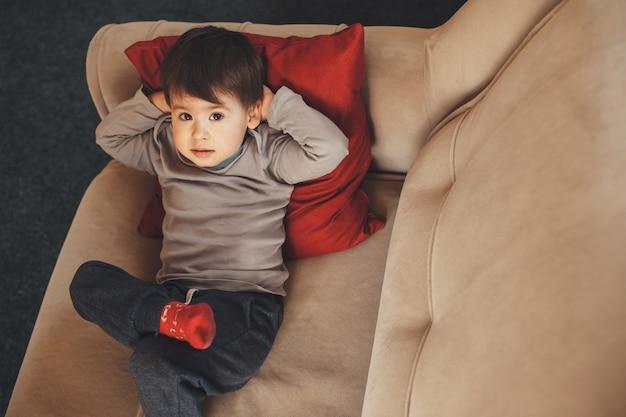Bovenaanzicht portret van een blanke jongen liggend op de bank en op zoek naar de camera