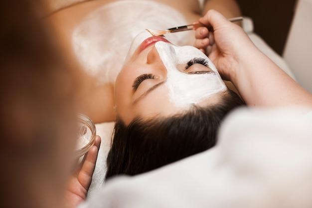 Bovenaanzicht portret van een charmante vrouw doet een wit anti-acnemasker in een wellnesscentrum.