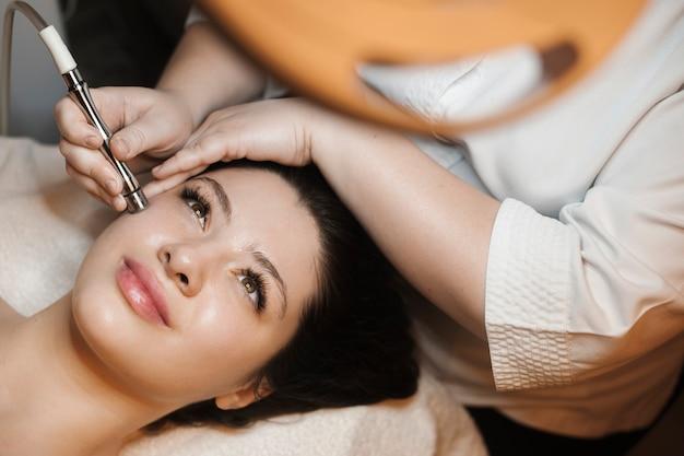 Bovenaanzicht portret van een mooie vrouw leunend op een bed met ogen open terwijl ze niet-invasieve microdermabrasie op haar gezicht in een spa salon.