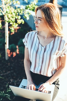 Bovenaanzicht portret van gember vrouw met sproeten en bril iets typen op de computer