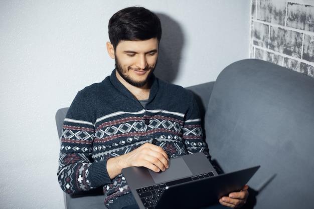 Bovenaanzicht portret van jonge lachende man, zittend thuis op de bank