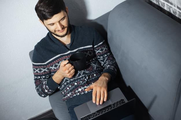 Bovenaanzicht portret van jonge zelfverzekerde man met zwarte mok in de hand