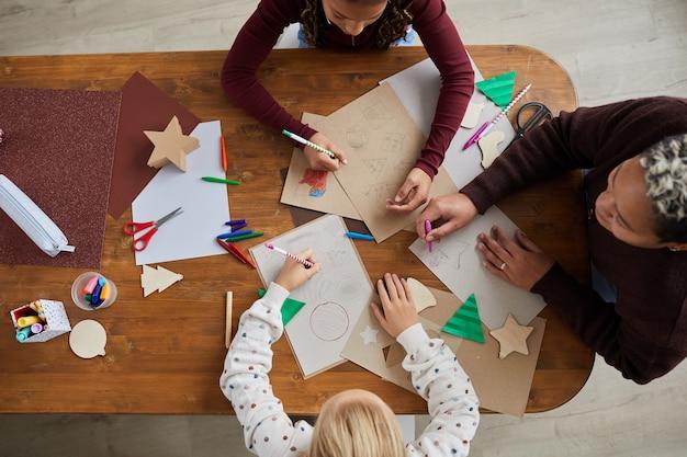 Bovenaanzicht portret van kinderen tekenen van afbeeldingen tijdens kunst- en ambachtles op school, kopie ruimte