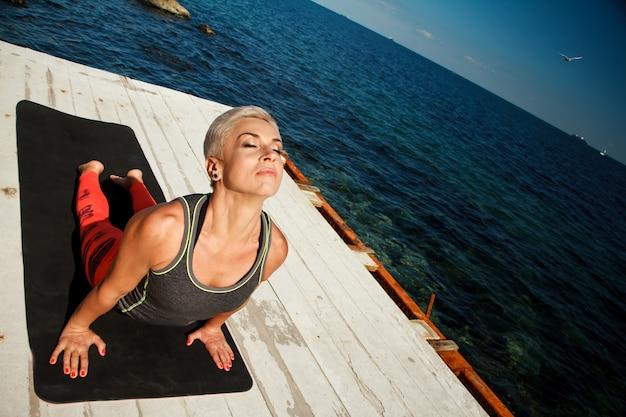 Bovenaanzicht portret van volwassen blonde vrouw met kort kapsel praktijken yoga op de pier tegen de achtergrond van de zee en de blauwe hemel