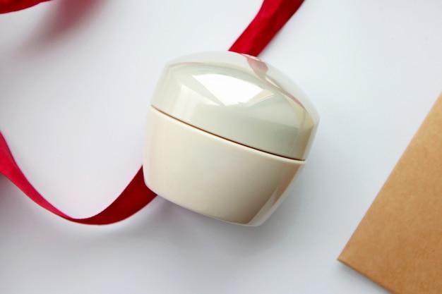 Bovenaanzicht pot parel kleur voor crème met een rood lint