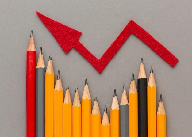 Bovenaanzicht potloden en rode pijl