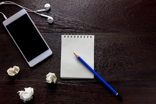 Bovenaanzicht potlood, notitiepapier, witte smartphone, zwarte koffie, oortelefoons, verfrommeld papier op kantoor bureau met kopie ruimte.