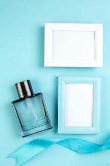 Bovenaanzicht presenteert fotolijsten met parfum op blauw oppervlak vrouw cadeau paar gevoel kleur parfum huwelijk liefde