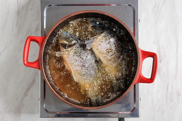Bovenaanzicht proces goudvis bakken op hete olie, thuis koken in de keuken gebakken vis maken met aziatisch recept