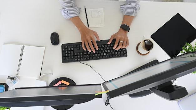 Bovenaanzicht programmeur bezig met ontwikkelaar ruimte met computer en apparaatscherm.