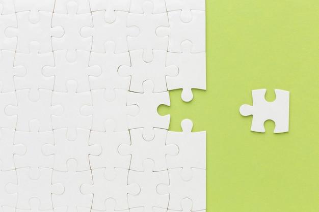 Bovenaanzicht puzzel met een stuk ernaast