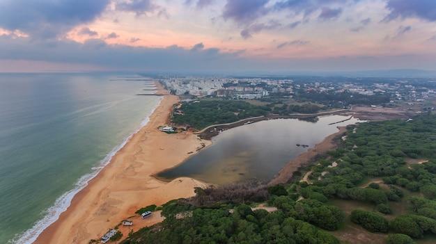 Bovenaanzicht quarteira strand met toeristen op de zee.