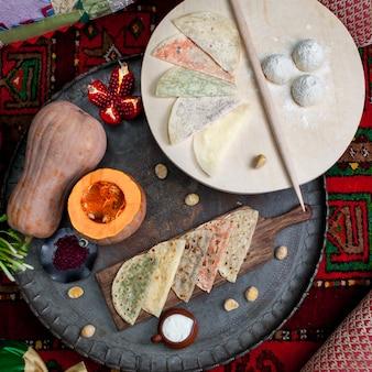 Bovenaanzicht qutab geassorteerd met pompoen en granaat en deegplank in snijplank