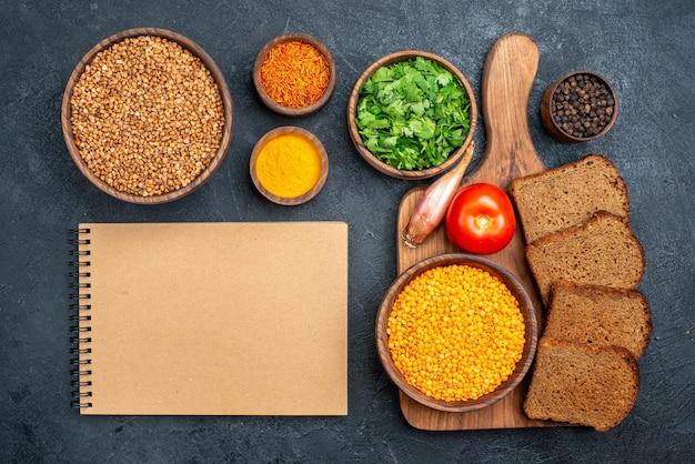 Bovenaanzicht rauw boekweit met groenten en brood op donkergrijs bureau