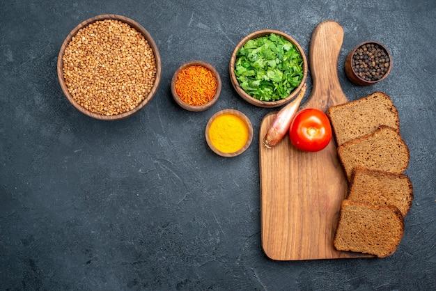 Bovenaanzicht rauw boekweit met groenten en brood op donkergrijze ruimte