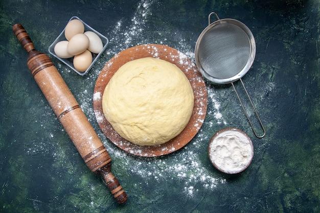 Bovenaanzicht rauw deeg met witte bloem en eieren op donkerblauwe achtergrond gebak bak taart taart rauw vers ovendeeg hotcake
