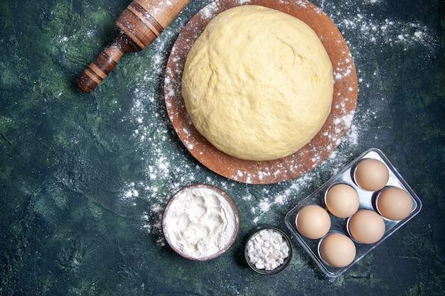 Bovenaanzicht rauw deeg met witte bloem en eieren op een donkerblauwe achtergrond gebak bak cake rauw ovendeeg hotcake pie vers
