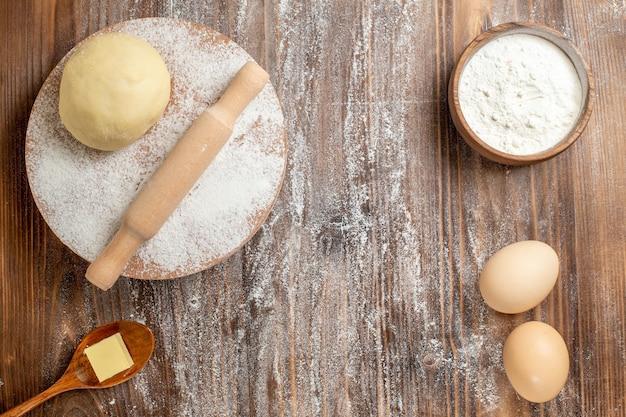 Bovenaanzicht rauw deeg stuk met bloem en eieren op houten bureau maaltijdmeel bakken deeg