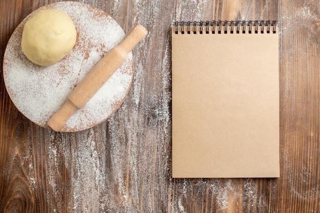 Bovenaanzicht rauw deegstuk met bloem op houten bureau maaltijdmeel bakdeeg