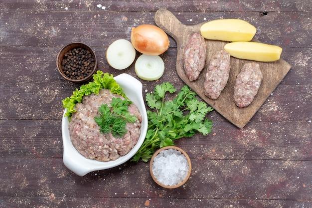 Bovenaanzicht rauw gehakt vlees met groenen binnen plaat met uien rauwe aardappelen zout op de bruine tafel vlees rauwkost maaltijd groen