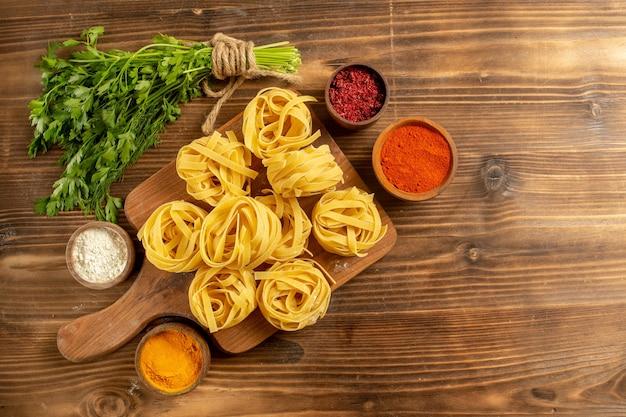 Bovenaanzicht rauw pastadeeg met kruiden en greens op een bruine achtergrond deeg maaltijd deegwaren rauw voedsel Gratis Foto