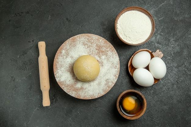 Bovenaanzicht rauw rond deeg met bloem en eieren op grijze achtergrond meelvoedsel deeg rauwe maaltijd