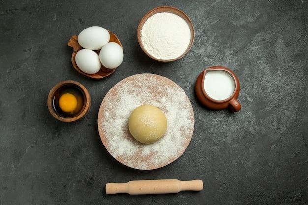 Bovenaanzicht rauw rond deeg met eieren en bloem op grijze achtergrond de maaltijdmeel van het voedseldeeg