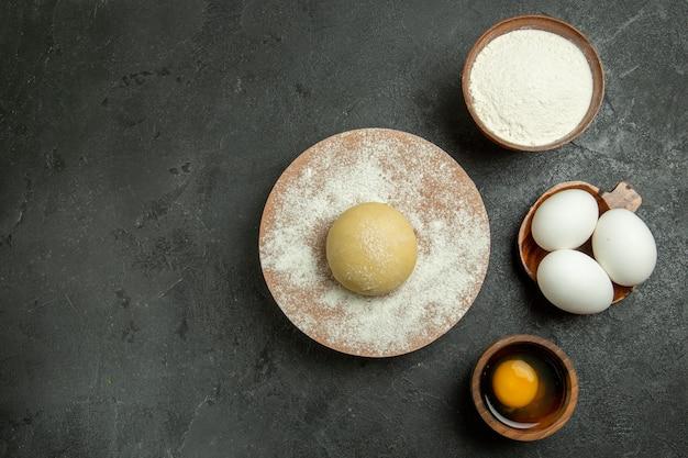 Bovenaanzicht rauw rond deeg met eieren en bloem op grijze achtergrond voedseldeeg maaltijd rauwe bloem