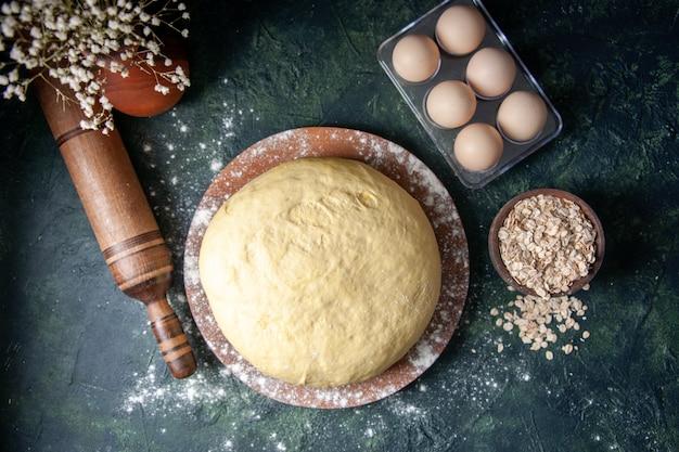 Bovenaanzicht rauw vers deeg op donkerblauwe achtergrond gebak bak cake rauw ovendeeg hotcake pie vers