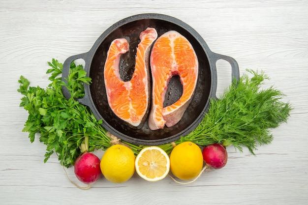Bovenaanzicht rauw vlees plakjes in pan met groenen op witte achtergrond