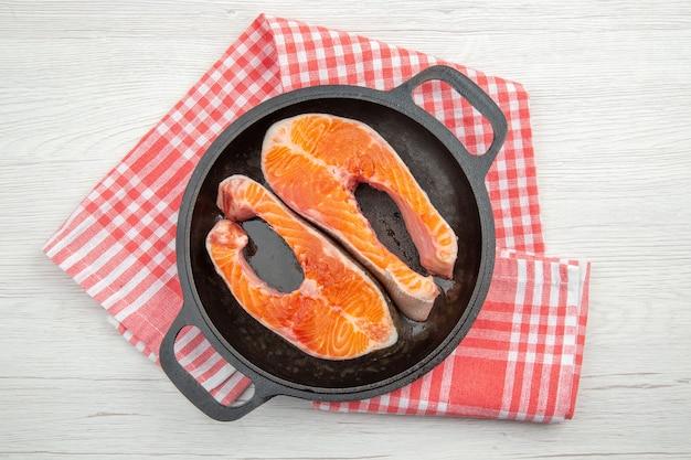 Bovenaanzicht rauw vlees plakjes in zwarte pan op witte achtergrond