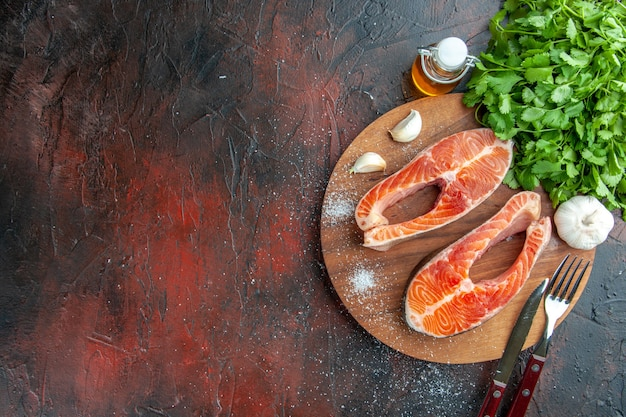 Bovenaanzicht rauw vlees plakjes met greens op een donkere achtergrond