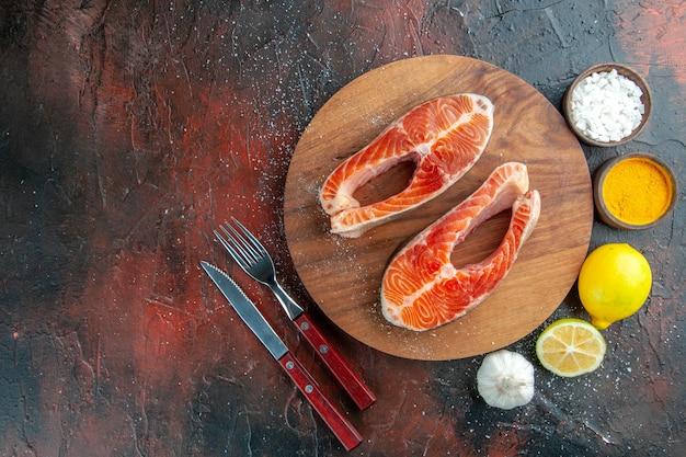 Bovenaanzicht rauw vlees plakjes met kruiden en citroen op donkere achtergrond