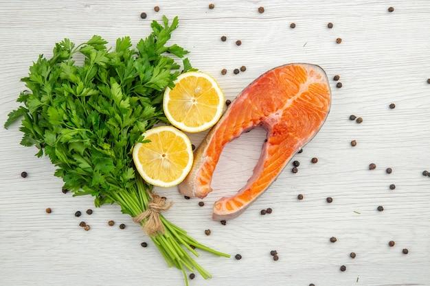 Bovenaanzicht rauw vlees segment met greens en citroen op witte achtergrond