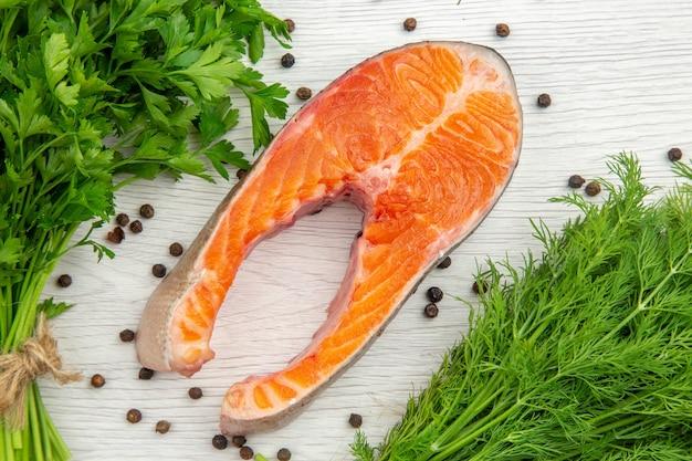 Bovenaanzicht rauw vlees segment met greens op een witte achtergrond