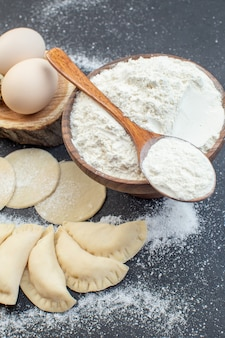 Bovenaanzicht rauwe aardappel hotcakes met eieren en bloem op donkere achtergrond taartdeeg koken biscuit oven cake eten bakken