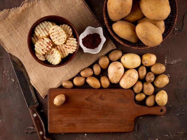 Bovenaanzicht rauwe aardappelen met gedroogde chili vlokken en mes op bruine achtergrond