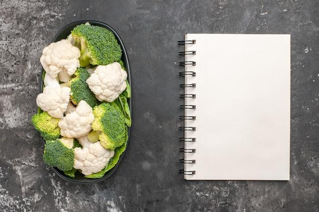 Bovenaanzicht rauwe broccoli en bloemkool op zwarte ovale plaat een notitieboekje op donkere ondergrond