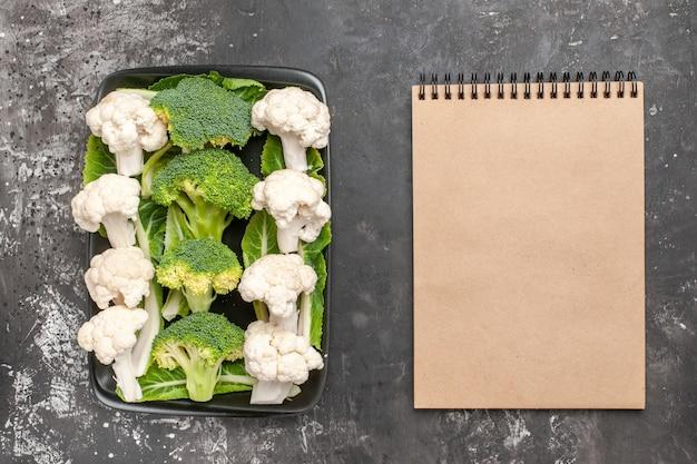 Bovenaanzicht rauwe broccoli en bloemkool op zwarte rechthoekige plaat een notitieboekje op donkere ondergrond