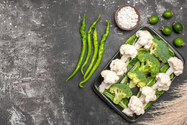Bovenaanzicht rauwe broccoli en bloemkool op zwarte rechthoekige plaat groene hete pepers zeezout feykhoas op donkere ondergrond vrije ruimte voedsel foto
