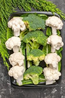 Bovenaanzicht rauwe broccoli en bloemkool op zwarte rechthoekige plaat op donkere oppervlak voedsel foto
