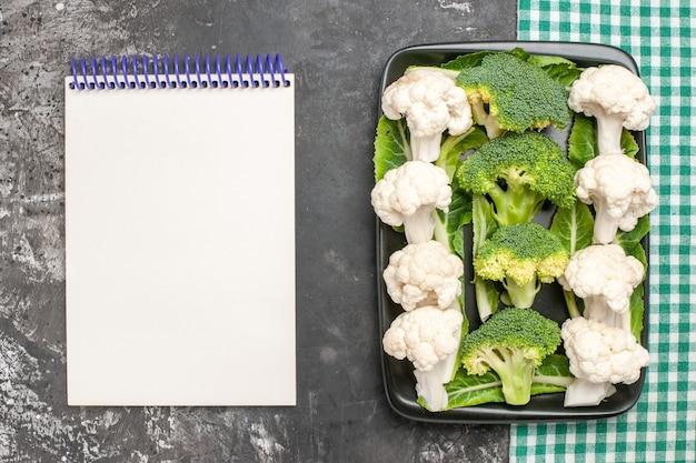 Bovenaanzicht rauwe broccoli en bloemkool op zwarte rechthoekige plaat op groen en wit geruit servet een notitieboekje op donkere ondergrond