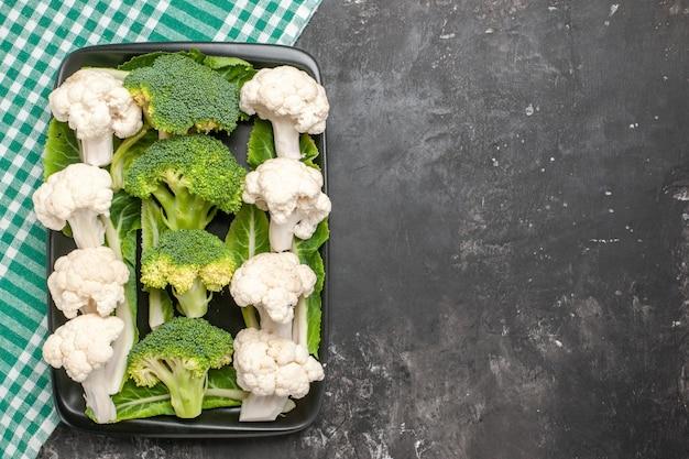 Bovenaanzicht rauwe broccoli en bloemkool op zwarte rechthoekige plaat op groen en wit geruit servet op donkere ondergrond met kopie ruimte