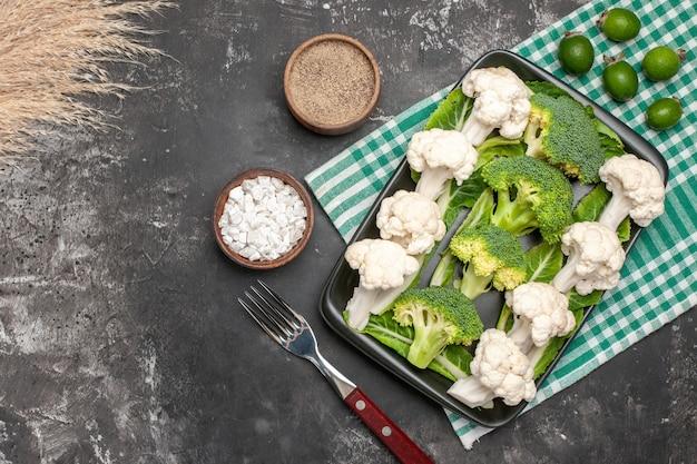 Bovenaanzicht rauwe broccoli en bloemkool op zwarte rechthoekige plaat op groen en wit geruit servet vork zeezout peper feykhoas op donkere oppervlakte vrije ruimte