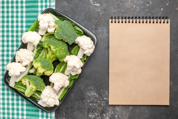 Bovenaanzicht rauwe broccoli en bloemkool op zwarte rechthoekige plaat op groen en wit geruit tafelkleed een notitieboekje op donkere ondergrond