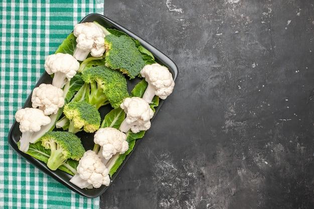 Bovenaanzicht rauwe broccoli en bloemkool op zwarte rechthoekige plaat op groen en wit geruit tafelkleed op donkere ondergrond vrije plaats