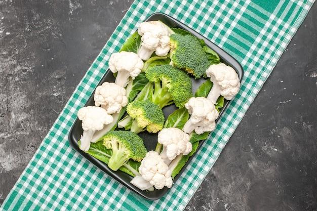Bovenaanzicht rauwe broccoli en bloemkool op zwarte rechthoekige plaat op groen en wit geruit tafelkleed op donkere ondergrond