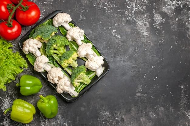 Bovenaanzicht rauwe broccoli en bloemkool op zwarte rechthoekige plaat tomaten groene paprika sla op donkere ondergrond vrije plaats