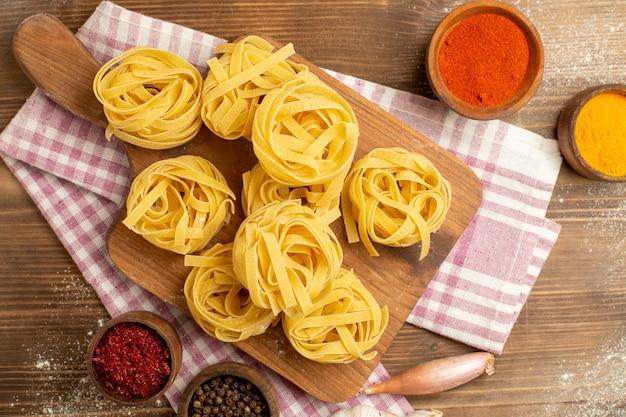 Bovenaanzicht rauwe deeg bloem gevormde pasta met kruiden op een houten achtergrond deeg maaltijd voedseldeegwaren